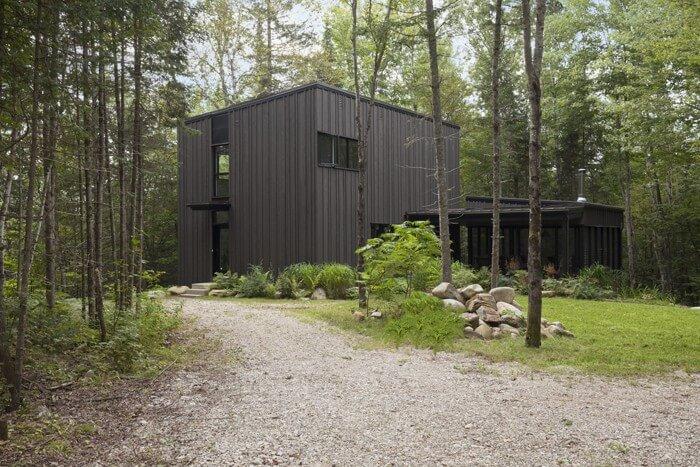 خانه چوبی به رنگ تیره در جنگلی با درختان صنوبر