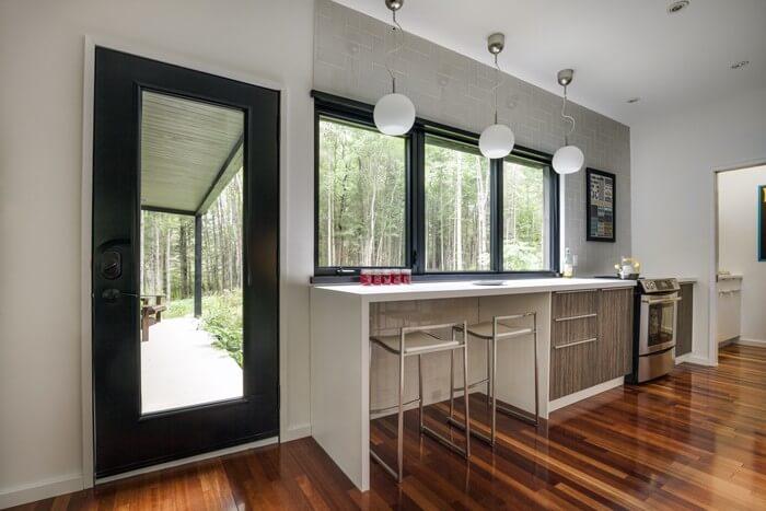 خانه چوبی به رنگ تیره در جنگلی با درختان صنوبر + تصاویر