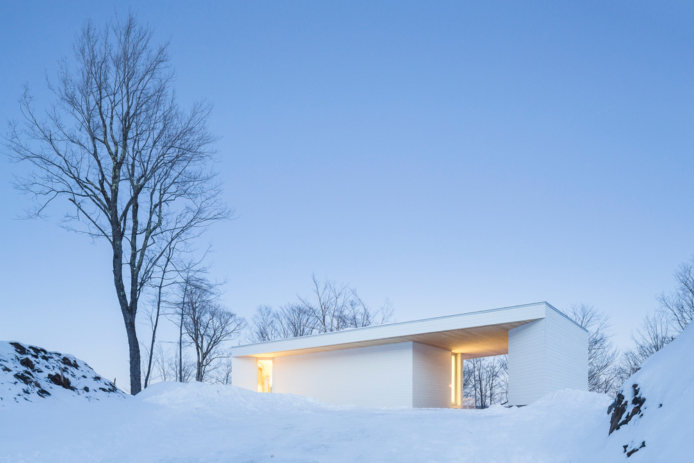 خانه مدرن و سفید با چشم انداز زمستانی در کبک کانادا