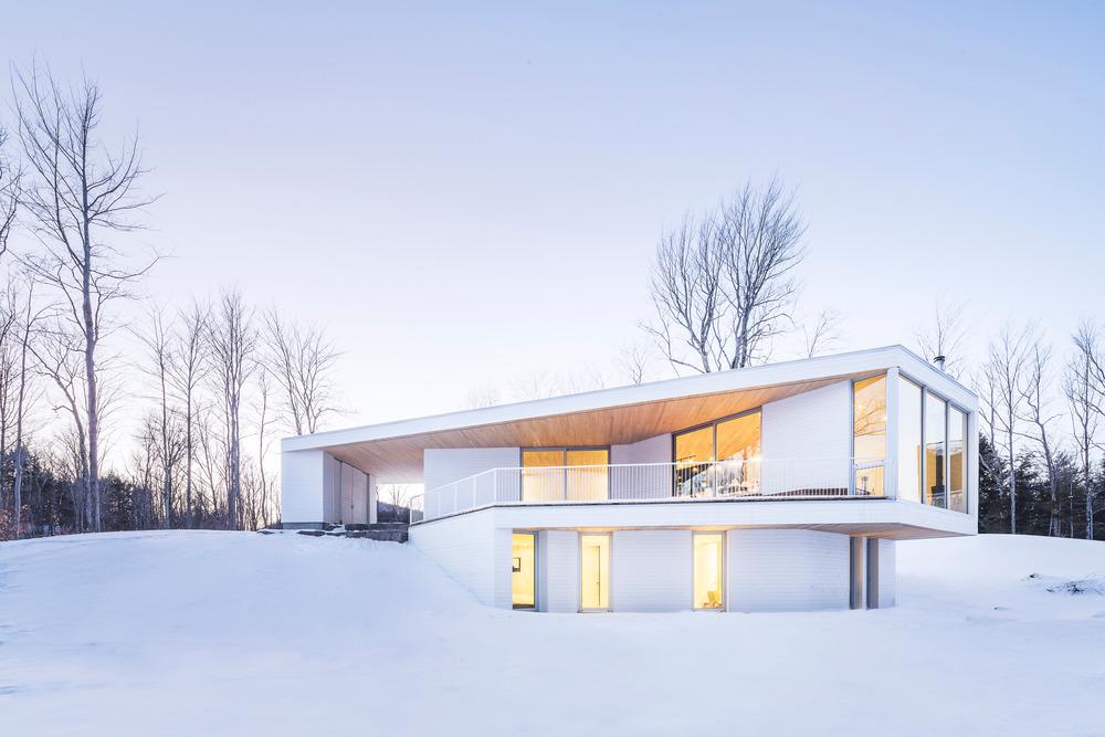 خانه مدرن و سفید با چشم انداز زمستانی در کبک کانادا + تصاویر