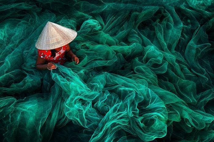 زنی با کلاه مخروطی در حال ساخت تور ماهیگیری - ویتنام