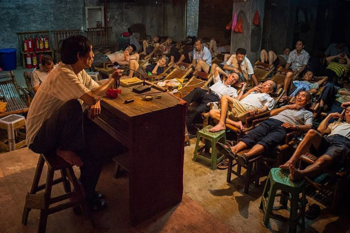 عکسی که در یک چای خانه در چین گرفته شده است. افراد با آرامش تمام در حال گوش کردن به داستان سرایی هستند.